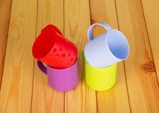 4 красочных пластичных чашки на предпосылке светлой древесины Стоковая Фотография