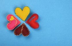 4 красочных сердца искусства ремесла войлока на сини Стоковое фото RF