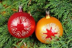 2 красочных шарика рождества на зеленых иглах сосны Стоковые Изображения RF