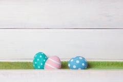 3 красочных handmade пасхального яйца лежат на зеленой лужайке на белой деревянной предпосылке Стоковая Фотография