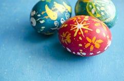 3 красочных handmade пасхального яйца изолированного на голубой предпосылке Стоковая Фотография RF
