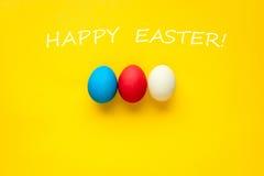 3 красочных handmade пасхального яйца на оранжевой предпосылке С словами счастливой пасхой Стоковое Фото