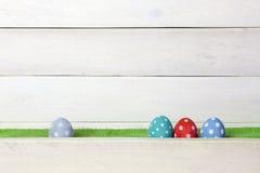 4 красочных handmade пасхального яйца стоят на зеленой лужайке в ряд на белой деревянной предпосылке с космосом на верхней части Стоковое фото RF