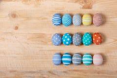 12 красочных handmade пасхальных яя на деревянной предпосылке с космосом вышли плоский стиль положения Стоковые Фото