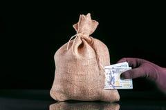 Красть деньги Потеря денег, разрыв в сумке, мешок денег с отверстием и рука хватая кучу банкнот доллара стоковые фото