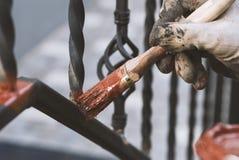 Крася выкованные перила на лестницах на входе дома Защита против ржавчины Стоковые Фото