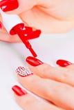 Крася заполированность на перстах с красными ногтями Стоковые Изображения