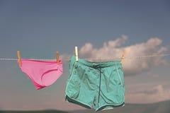 Краткость и брюки вися на зажимке для белья сухой на веревке для белья стоковые фотографии rf