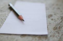 Кратко белая бумага и карандаш помещенные на увяданной старой деревянного стола Стоковое Изображение