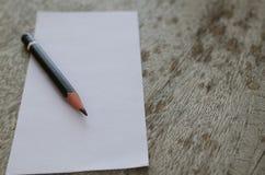 Кратко белая бумага и карандаш помещенные на увяданной старой деревянного стола Стоковые Изображения RF