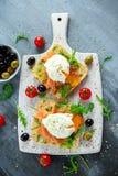 Краденное яичко на зажаренной здравице с копчеными семгами, rucola, оливками и овощами на белой доске завтрак здоровый Стоковое фото RF
