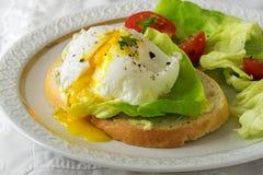 Краденное яичко с идущим желтком на куске багета с салатом и t Стоковая Фотография