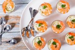 Креветка стопки с соусом тартара - легким рецептом коктеиля для праздничной партии, на белом диске с ложками на старой белой дере Стоковое Изображение RF