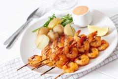 Креветки на белой плите с картошками Стоковое Фото