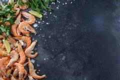 Креветки с известкой, льдом, травами и солью моря на черной предпосылке Рамка для вашего текста Креветка с травами и специями раз Стоковые Изображения RF