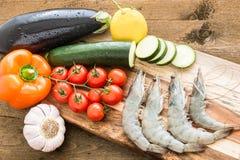 Креветки с овощами на деревянной доске Стоковые Изображения