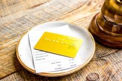 Кредитная карточка для оплачивать, кольца кельнера и проверки на des кафа деревянном Стоковое Изображение