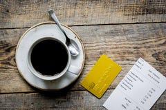 Кредитная карточка для оплачивать, кофе и проверки на bac стола кафа деревянном Стоковые Фото