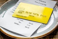 Кредитная карточка для оплачивать, плиты, стекел и проверки на ба стола кафа Стоковые Фото