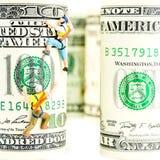 100 кренов доллара и 2 миниатюрных альпиниста Стоковое фото RF