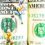 100 кренов доллара и 2 миниатюрных альпиниста Стоковое Фото