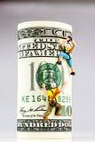 100 кренов доллара и 2 миниатюрных альпиниста Стоковые Фото