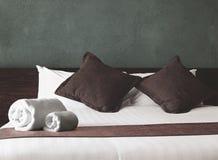 Крены и подушки полотенца на кровати Стоковая Фотография