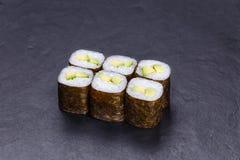 Крены суш при авокадо, который служат на черном каменном шифере японско стоковые изображения