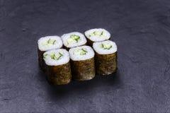 Крены суш при огурец, который служат на черном каменном шифере японско стоковые фото