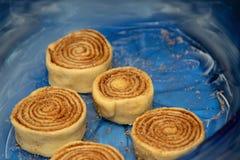 Крены циннамона заготовки в голубом прозрачном печь блюде стоковая фотография rf