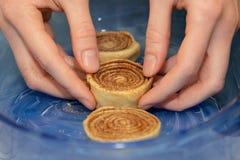 Крены циннамона заготовки помещены в голубом прозрачном печь блюде стоковые изображения
