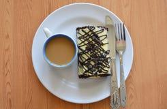 Крен варенья шоколада заполнил сливк и кофе с ножом таблицы на блюде Стоковое Изображение RF