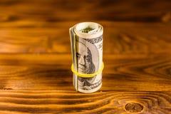 Крен 100 долларовых банкнот с резиной на деревянном столе Стоковые Фотографии RF