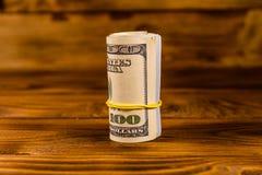Крен 100 долларовых банкнот с резиной на деревянном столе Стоковое Изображение