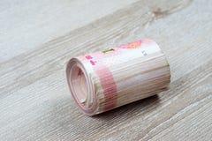 Крен 100 китайских банкнот юаней на деревянном столе Стоковые Изображения