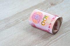 Крен 100 китайских банкнот юаней на деревянном столе Стоковое фото RF