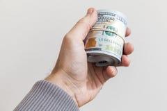 Крен новых 100 долларов примечаний в руке Стоковая Фотография RF