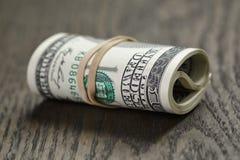 Крен новых долларовых банкнот стиля 100 на таблице Стоковая Фотография RF