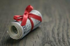 Крен 100 долларовых банкнот на деревянном столе Стоковые Фотографии RF