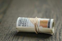 Крен 100 долларовых банкнот на деревянном столе Стоковые Изображения