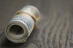 Крен 100 долларовых банкнот на деревянном столе Стоковые Фото
