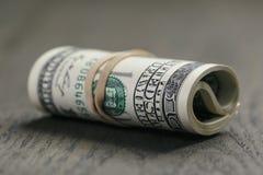 Крен 100 долларовых банкнот на деревянном столе Стоковые Изображения RF
