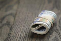 Крен 100 долларовых банкнот на деревянном столе Стоковая Фотография