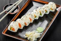 Крен суш - суши Maki сделанные из плавленого сыра семг, апельсина, авокадоа и на темной деревянной предпосылке Стоковые Фото