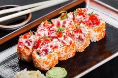 Крен суш - суши Maki сделанные из тунца, красного плавленого сыра икры, огурца, авокадоа и на темной деревянной предпосылке Стоковое Фото