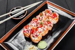 Крен суш - суши Maki сделанные из тунца, красного плавленого сыра икры, огурца, авокадоа и на темной деревянной предпосылке Стоковое Изображение RF