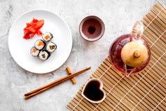 Крен суш с семгами и авокадоом на плите с соевым соусом, палочкой, wasabi около бака чая на серой каменной верхней части предпосы Стоковое Изображение RF