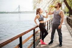 Крепкие и красивые люди расслабляющие и имеющ пролом Они питьевая вода Человек и женщина стоят дальше Стоковое фото RF