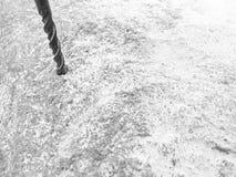 Крепкое, сверла бурового наконечника утюга вольфрамокарбидного сплава отверстие в большом сером камне Близкий взгляд зелень genti стоковые фотографии rf
