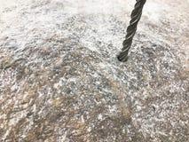 Крепкое, сверла бурового наконечника утюга вольфрамокарбидного сплава отверстие в большом сером камне Близкий взгляд зелень genti стоковые фото